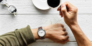 time management tips skills man looking at watch drinking coffee